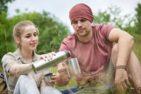 man drinking water: two travelers with thermos Stock Photo
