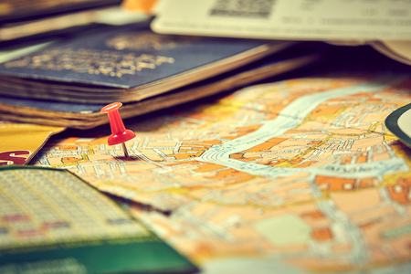 pins marking travel itinerary points on map and passport Foto de archivo