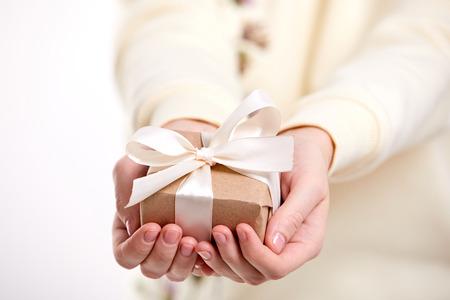 manos sosteniendo caja de regalo artesanal