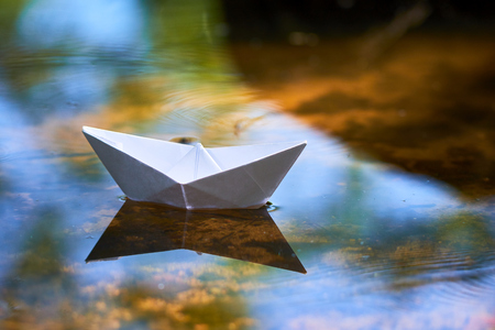 paper boat on the water Imagens