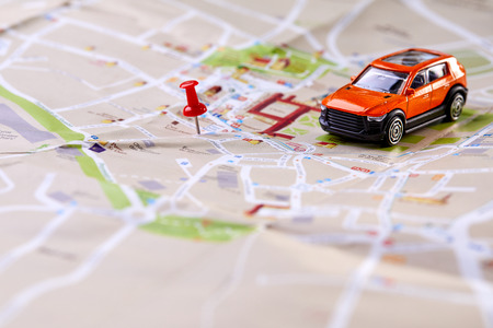 travel concept - small toy car on the map Standard-Bild