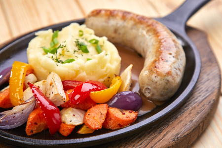 sausage with mashed potato and vegetables, wooden background