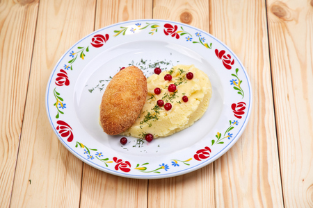 cutlet with mashed potatoes on the wooden background
