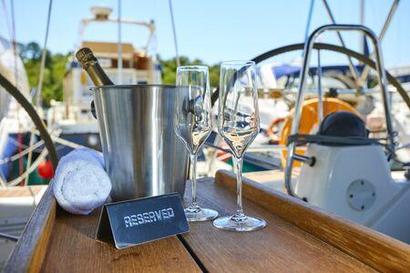 Romantischer Luxusabend auf Kreuzfahrtyacht mit Champagnereinstellung. Leere Gläser und Flasche mit Champagner und tropischem Sonnenuntergang mit Meereshintergrund
