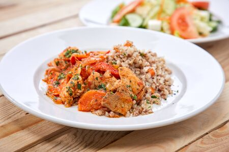 meat with buckwheat and salad on the wooden background