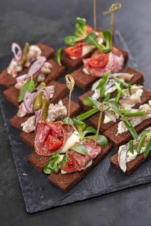 Canape with meat and vegetables on black