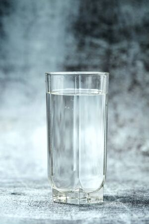 Glass of pure water on the grey background