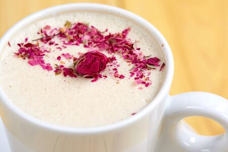 tasty cappuccono with rose petals Фото со стока