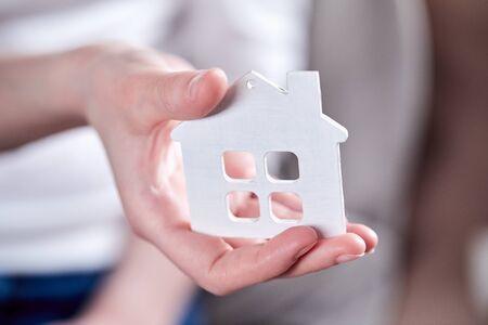 Female hands holding model of house