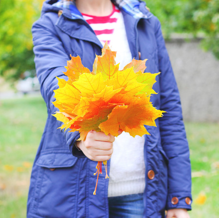 Autumn leaves in hand girl