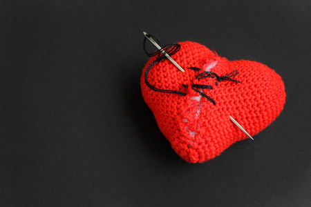 Broken red heart sewn with thread