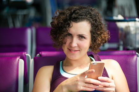 business traveller: Beautiful girl with phone in hand waiting for the plane at the airport. Stock Photo