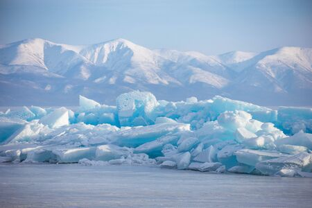 Emerald ice floe on the background of high mountains in Baikal lake