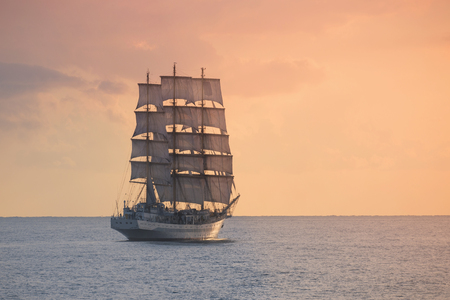 Ancient sailing ship in the sea at sunset Banco de Imagens