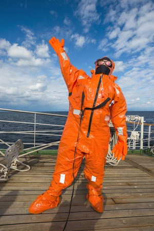 Girl in a survival suit on the deck of a sailboat in the ocean Banco de Imagens