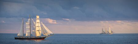 Panorama of sailboats in the sea at sunset