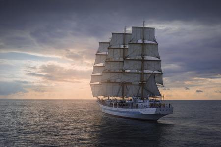 석양 바다에서 고대의 항해 배 스톡 콘텐츠