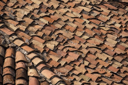 Old clay tiles on the roof of a house in Bulgaria. Background