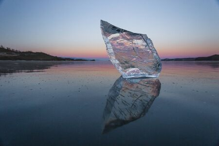 A piece of clear ice on Lake Baikal at sunset