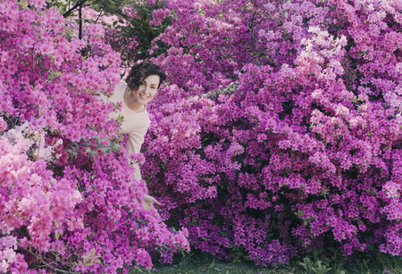 Beautiful girl and flowering rhododendron Banco de Imagens