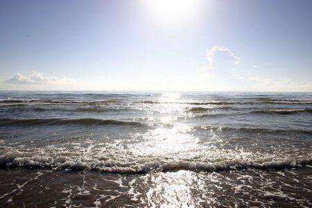 glistening: Sol brillando sobre las olas como que rodar en la playa
