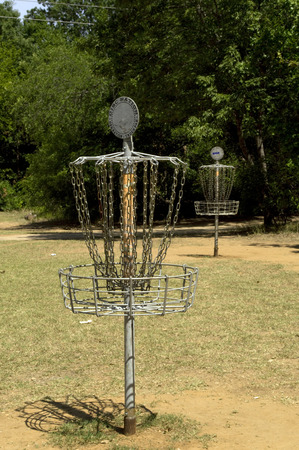disc golf: A pair of disc golf baskets in a park on a sunny day