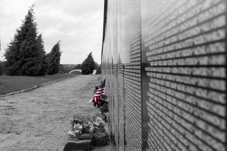 Drapeau américain placée pour honorer un nom à un mur commémoratif de guerre du Vietnam sur un jour couvert nuageux