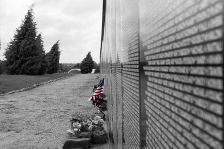 US Flag placed to honor a name at a Vietnam War Memorial Wall on a cloudy overcast day Stock Photo