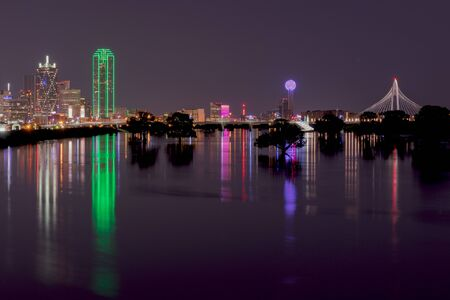 nightime: Long exposure photo of the lights of the Dallas Texas skyline reflecting on the flooded Trinity River with trees in the river silhouetted by the glowing reflection.