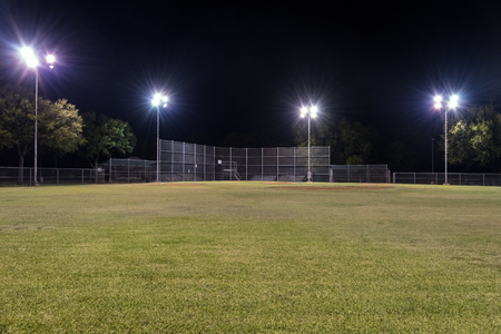 Night photo of an empty baseball field at night looking back toward home plate from right field with the lights on and contrasting against the blackness of the night sky. Stock Photo