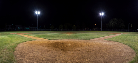 onto: Panorama night photo of an empty baseball field at night with the lights on taken behind home plate and looking out across the pitchers mound onto the field. Stock Photo