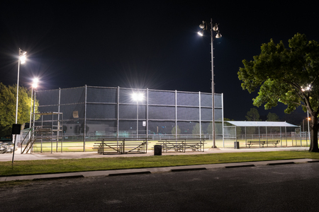 Night photo of an empty city park baseball field at night with the lights on as seen from the parking lot and the bleachers behind home plate.