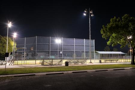 beisbol: Foto de la noche de un campo de béisbol parque de la ciudad vacía en la noche con las luces encendidas como se ve desde el estacionamiento y las gradas detrás del plato.