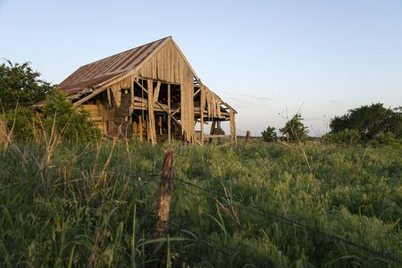 falling apart: Crumbling, broken down, ruins of a decaying barn with boards rotting and falling apart and sitting in a farm filed by the roadside at sunset beyond a fence in the foreground. Stock Photo