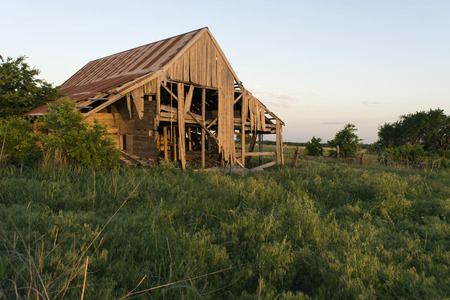falling apart: Crumbling, broken down, ruins of a decaying barn with boards rotting and falling apart and sitting in a farm filed by the roadside at sunset.