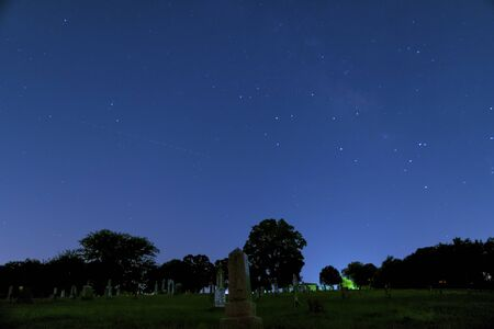 faintly visible: Long exposure, night photography of a the tombstones in a rural cemetery with a portion of the Milky Way faintly visible in the stars above the trees on the horizon.