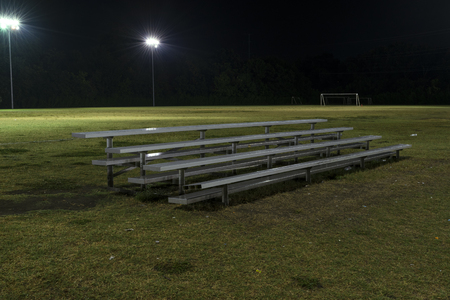 Metal bleachers on an empty soccer field at night with the lights on and water drops sparkling on the seats from a recent rain. Stock Photo