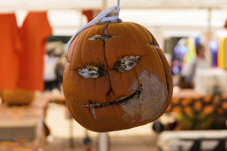 A creepy carved face on a Halloween pumpkin that had a smile before it started rotting and is now a smirk with empty, hollow eyes as it hangs on display at a pumpkin patch fall festival. Stok Fotoğraf