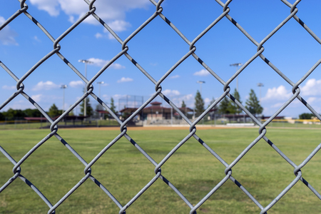 Looking through the diamond shaped pattern of holes on a metal, chain link fence at a baseball field on a beautiful, sunny day with some clouds drifting by in the sky. Stock Photo