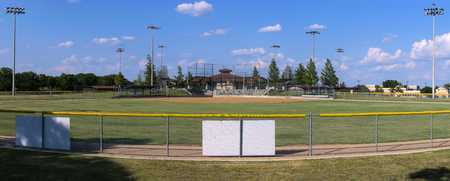 Panoramic view of an empty baseball field from a hill overlooking the fence in centerfield