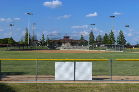 View of an empty baseball field from a hill overlooking the fence in centerfield Stock Photo