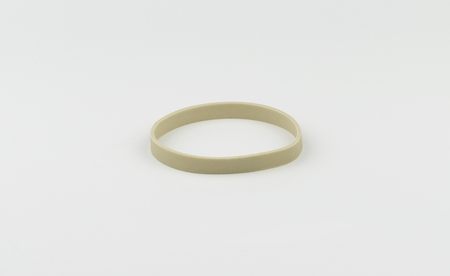 A single, beige latex rubber band on a white back ground ready to stretch and hold things together in office, school, or other uses.