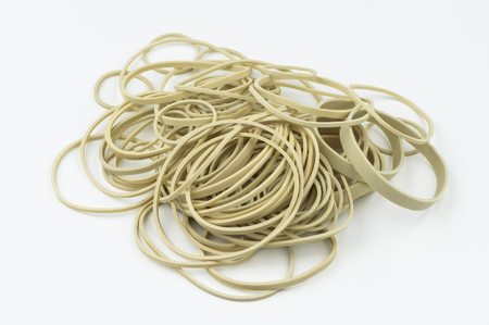 A stack of different sized latex, rubber bands on a white background ready for assorted uses in school, an office, or miscellaneous other environments.