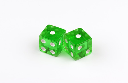 A pair of green, translucent gaming dice on a white background
