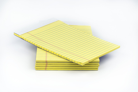 Yellow, ruled notepads neatly stacked with the top one offset that could be used for taking notes, or sharing ideas in school or office settings. Reklamní fotografie