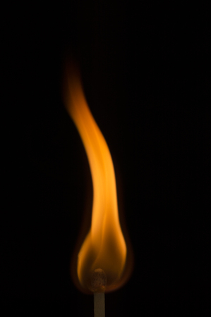 Long red, orange, and yellow flame curving up as the fire ignites on the tip of a wooden match against a black background. Stock Photo