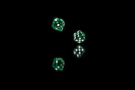 Two green, translucent, plastic game dice with white spots captured in the air as they are being rolled across a mirror with black background.