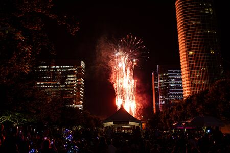 A glowing fountain of bright red sparks created by fireworks shooting into the air and reflecting off the surrounding buildings and creating red silhouettes of hte people in the crowd during the Independence Day Celebration at Klyde Warren Park in downtown Dallas, Texas.