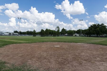 A view of a baseball field looking out across the diamond and pitchers mound from behind home plate on a summer afternoon with white clouds in the blue sky. Stock Photo