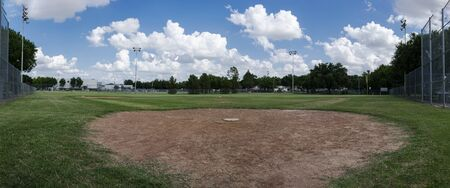 A panoramic photo of a baseball field looking from behind home plate out across pitchers mound and the diamond to outfield wiht fluffy clouds in the blue sky overhead.
